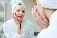 Young woman applying beauty cream (thumbnail)