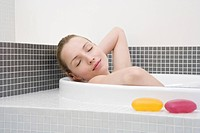 Young woman taking bath, eyes closed, side, view, portrait