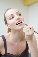 Young woman applying lipstick, portrait, close_up