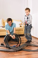 Father and son 4-5 playing with toy racetrack (thumbnail)