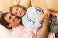 Father and son 4_5, relaxing on sofa, elevated view