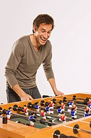 Young man playing tabletop soccer