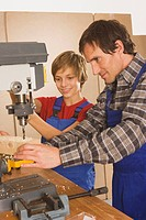 Germany, father and son , Working on drill machine