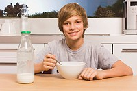 Teenage boy 13_14 having breakfast, portrait