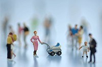 Female figurine with stroller among people, close up