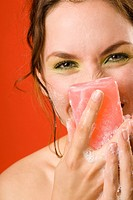 Young woman covering face with cake of soap, close up