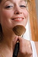 Young woman using make_up brush, close up