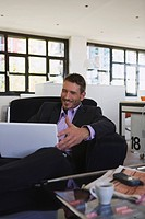 Business man in office using laptop, portrait