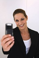 Business woman holding mobile phone, portrait