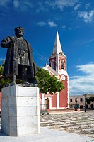 The majestic statue of a portuguese emperor in front of the red colored Chapel de Sao Paolo on the Ilha de Mocambique with blue sky(Island of Mozambiq...