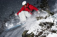Skier jumping over small rock