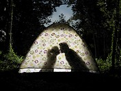 Silhouette of couple kissing in tent