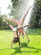 Girls playing under a water_jet