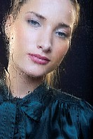 Portrait of smart young woman looking out of rain covered window