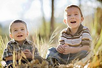 Two young boys laughing in field