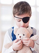 A young boy with brown hair wearing an eye patch embracing a teddy bear with a wound patch on its head