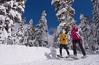 A couple snowshoeing on a sunny winter day with snow covered trees at Northstar near Lake Tahoe in California