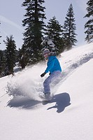 A woman snowboarding on a sunny day in fresh powder snow at Northstar near Lake Tahoe in California