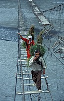 Traditional dressed women coming back from the harvest and walk over a gigantic suspension bridge in the karakorum mountains near Passu on the Karakor...