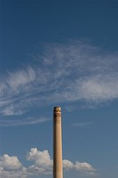 The top of a smokestack against a blue sky with puffy clouds in Duluth, Minnesota