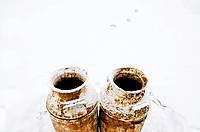 Two rusty jugs in snow, Maricourt, Quebec