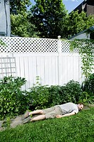 Man laying on a walkway in a backyard in front of a white picket fence, Montreal, Quebec