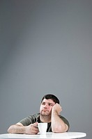 Man looking sad with a coffee at a table on a grey background