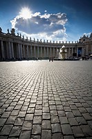 The cobblestone Piazza of the Basilica of Saint Peter with north west view of Gian Lorenzo Bernini´s colonnade, Vatican City, Italy.