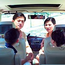 Parents and two children sitting in vehicle, face to face