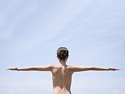 Topless young woman on beach, arms outstretched