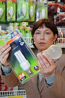 Woman with energy saving lamp and bulb