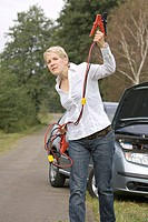 Woman beckoning with jumper cable
