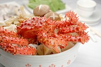 Close Up to a cooked king crab in white pot with raw hot pot ingredients under