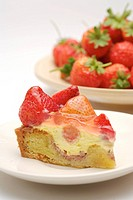 Piece of strawberry cake on plate and a dish of strawberries behind