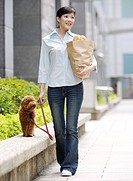 Young woman walking a Toy Poodle on sideway, holding bag of groceries