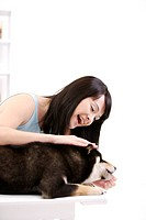 Young woman playing with a lying Akita Dog, side view
