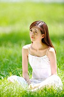 Portrait of young woman sitting on grass cross legged, looking away