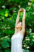 Young woman stretching arms up in woods, close_up