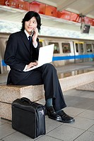 Businessman sitting on bench of train platform with a laptop on thigh, using cell phone