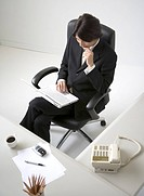 Overhead view of businessman sitting at desk with laptop on thigh