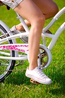 Young woman riding bicycle on grass, low section