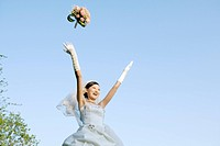 Young bride tossing bouquet, smiling