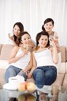 Four young women by sofa holding wineglasses, smiling, portrait