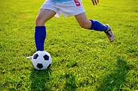 Soccer player kicking ball, mid section
