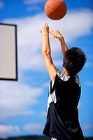 Teenage boy throwing basketball