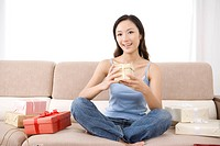 Young woman sitting on sofa with gifts
