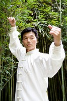 Man practicing Tai Chi in bamboo grove, portrait