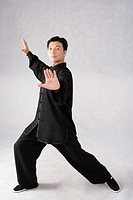 Man practicing Tai Chi against white background