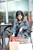 Young woman sitting by shopping bags