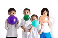 Four children blowing balloons, portrait
